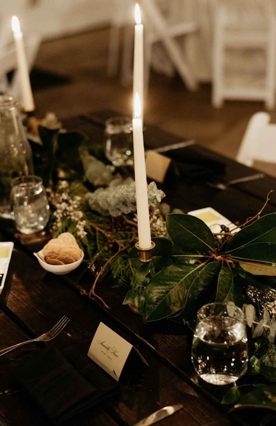 Elegant reception tables with greenery runners and candles  | Image by Laurken Kendall