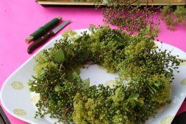 Dieser Kranz aus grünen Holunderbeeren und Frauenmantel schmückt – je nach Größe – Tür, Tor oder Eingangsbereich. Aus Blütenständen, Dolden und Ranken ist er schnell gebunden.