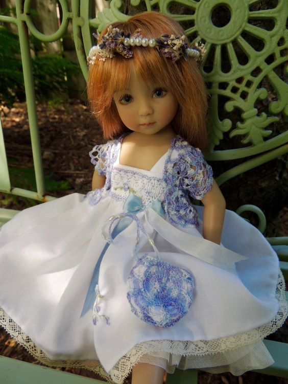 "Little Darling 13"" doll by Effner models an ensemble by Chiditta Designs.  The batiste dress is hand smocked, with hand embroidery in shades of lavender & soft blues on its bodice.  It has antique lace and a soft tulle double-frill pettislip.  Hand-crocheted bolero and purse echo the colors of the smocking and embroidery.  The hair garland has pearls, with dried lavender and baby's breath. Pin created by Nancy Lee Moran in 2016"