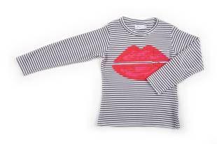 Camiseta para niña con diseño de rayitas grises y blancas. Mangas largas. Al frente, estampado con unos labios rojos.