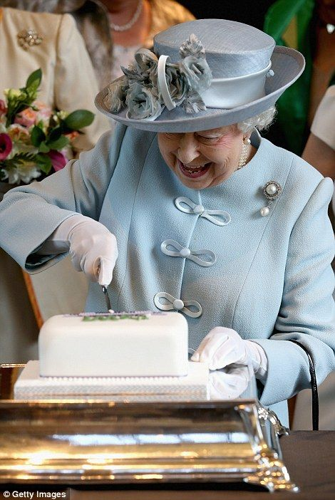 Doing it justice: The Queen beams as she cuts into the cake during the ...