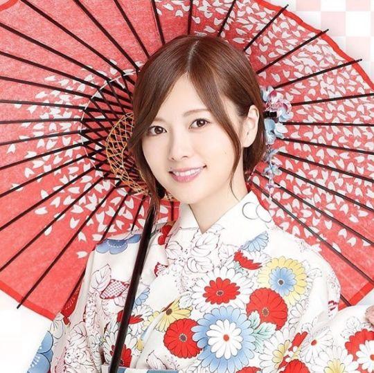 赤い和傘をさす白石麻衣