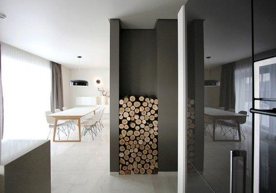 rack moderne de rangement bois de chauffage et salle à manger blanche avec table en bois clair et chaises Eames