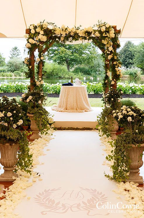This wood arbor laced with white roses, hydrangeas and green ivory brings the outdoors in.: