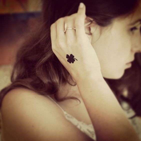 Tiny clover leaf temporary tattoo sticker on hand