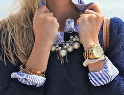Large scale jewelry.  Rolex style watch,  large pearls/metal balls on necklace with solid sweater and oxford.