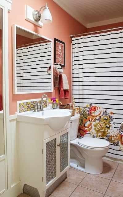 This rosy coral looks great with pinky-beige tile and I love the striped shower curtain with a hit of floral.