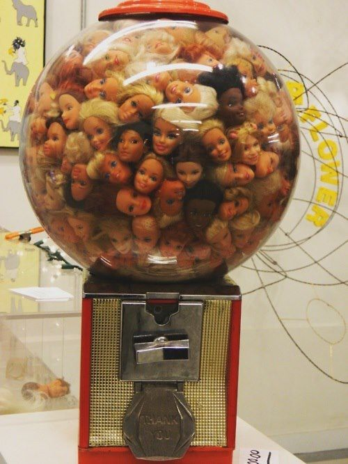 Barbie heads in a gumball machine is something highly unusual and something a person wouldn't expect, adding a contrast in the piece.