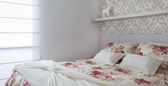 Com tons claros, o papel de parede com tema de folhagem ajuda a acalmar o quarto do casal. O enxoval florido complementa a decoração.