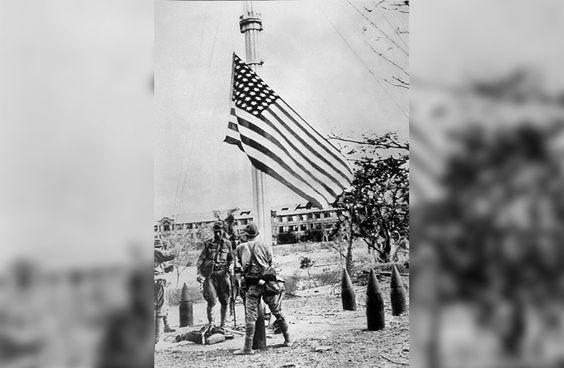 70 anos do fim da Segunda Guerra Mundial Legenda: Soldados japoneses retiram a bandeira americana nas Filipinas após invadirem a ilha (Keystone/Getty Images)