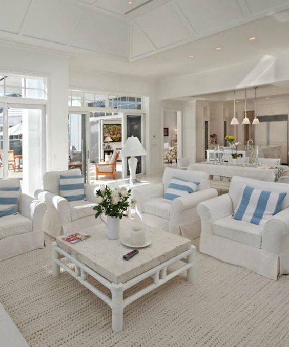 Chic, bright and airy living room in all white furniture and little blue in details - beach house design