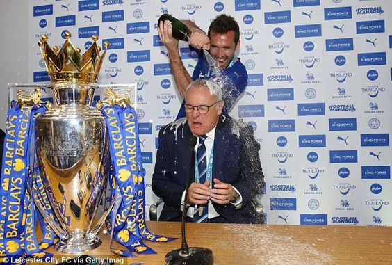 Leicester defender Christian Fuchs soaks  manager  Ranieri in champagne during his press conference