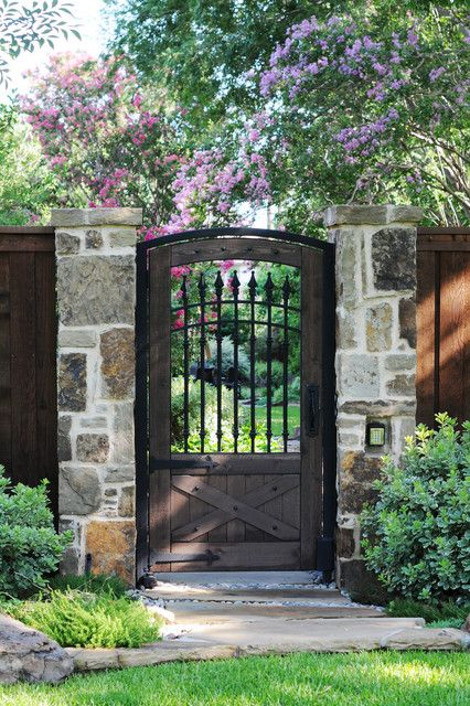 Garden gate ideas and French Country inspiration: an arched garden gate has wood and iron and is framed by stone posts. #gardengate #gardenideas #FrenchCountry #Provence #farmhouse