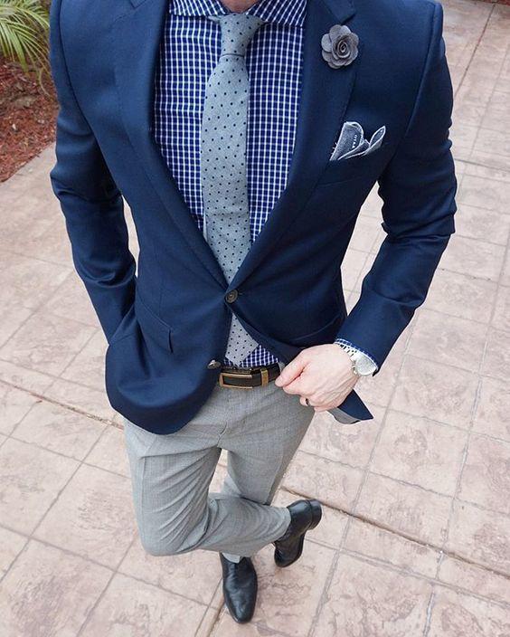 Acheter la tenue sur Lookastic: https://lookastic.fr/mode-homme/tenues/blazer-chemise-de-ville-pantalon-de-costume/20592   — Chemise de ville à carreaux bleue  — Broche à fleurs grise  — Cravate á pois gris  — Pochette de costume bleu clair  — Blazer bleu marine  — Ceinture en cuir brun foncé  — Pantalon de costume gris  — Chaussures richelieu en cuir noires