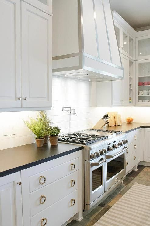 Brass Pulls Adorn White Shaker Cabinets Topped With Black Quartz Countertops Flanking A Stai Shaker Style Kitchen Cabinets Kitchen Hoods Kitchen Cabinet Styles