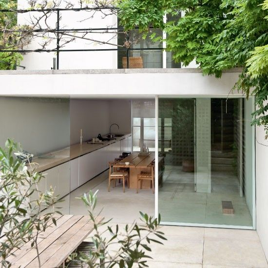 Kitchen and garden - the continuous flooring and the glass wall blends the transition #indooroutdoor