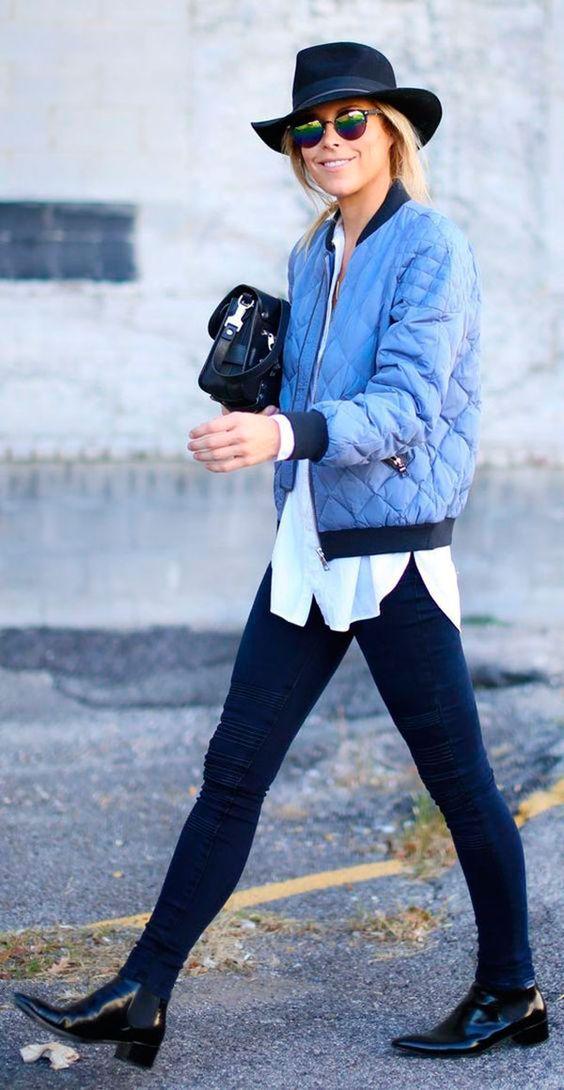 Mulher loira andando na rua usando calça jeans skinny preta, botas de verniz, camisa branca, jaqueta bomber azul serenity, bolsa proenza schouler e chapéu preto: