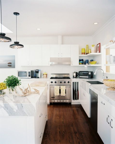 Marble bench top and white cabinetry in a bright kitchen