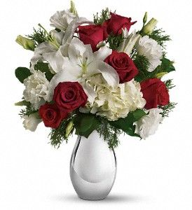 "This fashionably festive holiday bouquet features red roses and snowy white hydrangea, lilies and lisianthus in a sparkling silver reflections vase. The perfect gift for anyone who'd like tradition spritzed up with a little Christmas charisma.  The lovely Christmas bouquet includes white hydrangea, red roses, white oriental lilies and white lisianthus accented with flat cedar.  Approximately 14 1/2"" W x 17"" H  Orientation: One-Sided  As Shown : 67.95 Deluxe : 77.95 Premium : 87.95:"