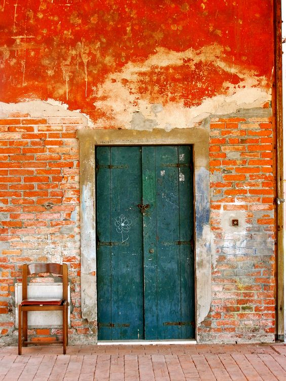 Street scene vibrant orange washed brick wall with teal painted wood door