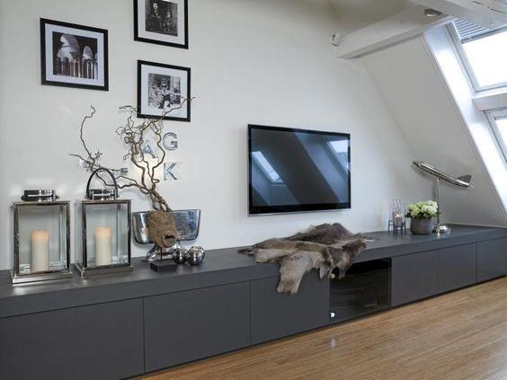 Langs den ene veggen i stuen er det montert en plassbygget tv benk ...
