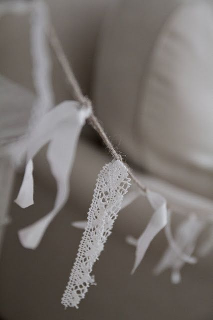 vintage ribbon tied onto jute string, would be pretty hanging across a window with a table under it and white flowers on the table