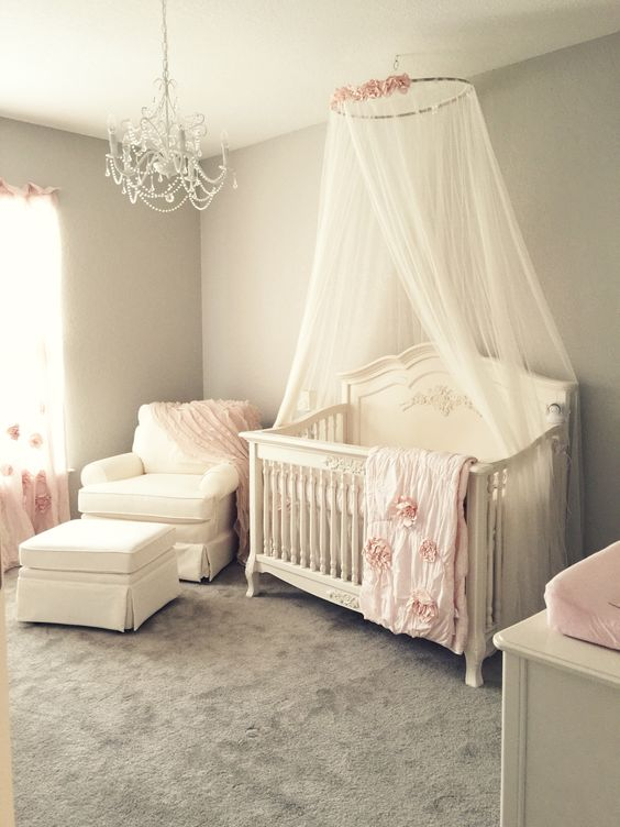 Girly pink blush nursery with chandelier, ivory rocker and glider ottoman, and ivory crib canopy