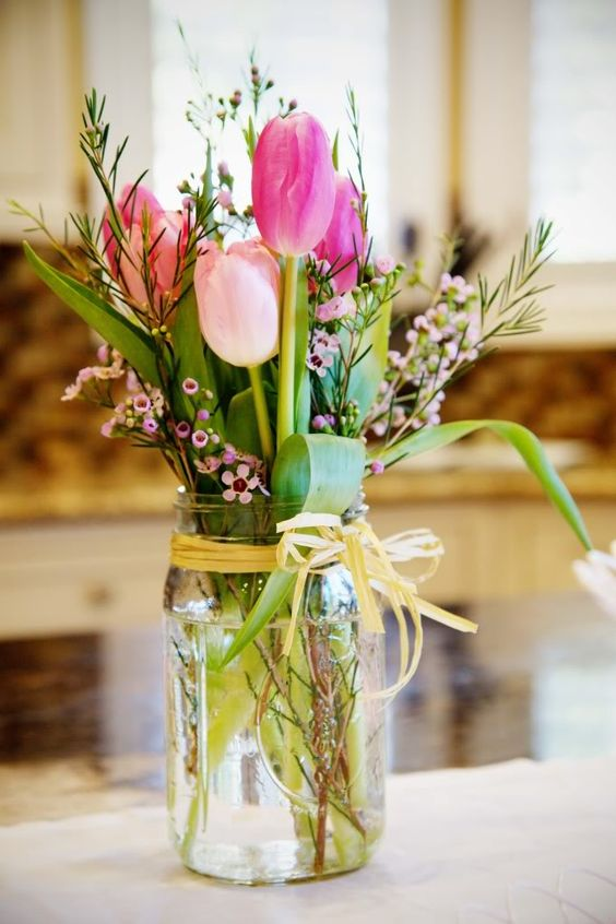 Simple, country-inspired summer flowers featuring pink roses and a mason jar for your next bridal or baby shower. An easy enough arrangement to create on your own.