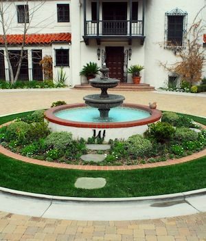 Water fountain surrounded with garden bed of rocks and for Front yard garden designs with water feature