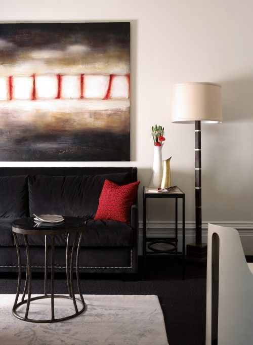 2. Use balance of color. This art has a lot of black with just a little bit of red. The black sofa with just a little red pillow keeps the same balance of colors as the art. Carrying that balance of color though the furnishings spreads the influence of the painting