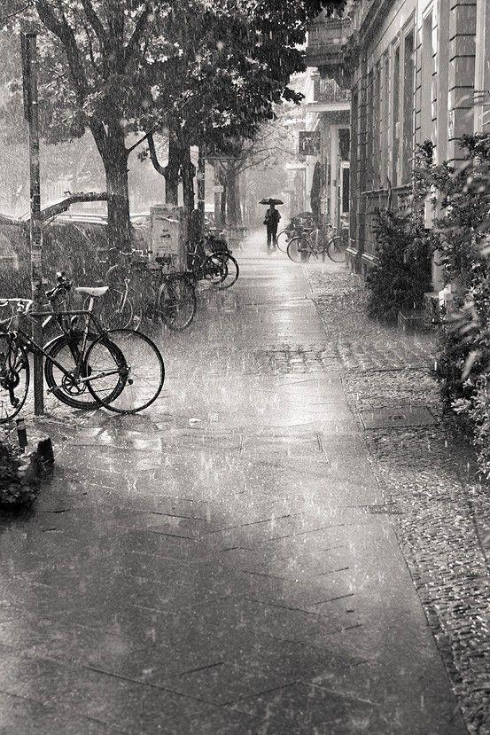 Paisatge en blanc i negre d'un carrer solitari, amb un home al fons. El fet que sigui en blanc i negre i que estigui plovent donen un estil dramátic al moment.: