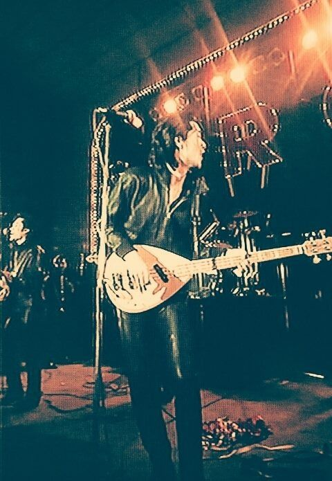 上下黒の衣装でギターを持っているリーゼントヘアの矢沢永吉の画像