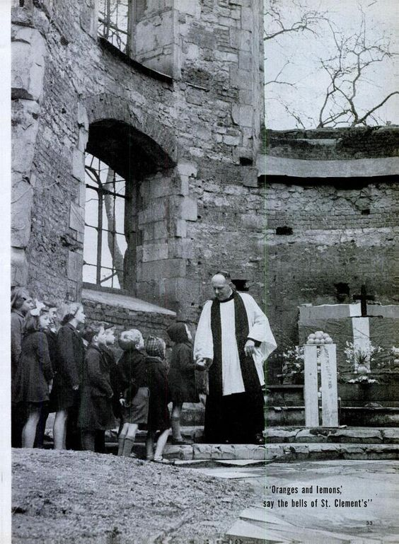 Rev. P.D. Ellis distributes oranges and lemons to 25 children in the bombed out church of St. Clement in London. March 31, 1944. LIFE photo.