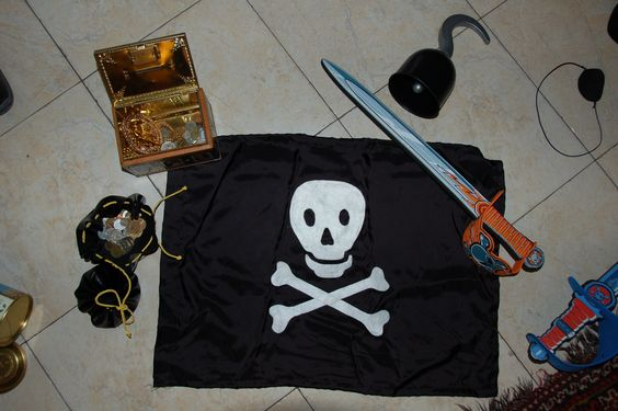 KIT PIRATA JAK & MAT 2:  Bandiera pirati con teschio, sacchetto del tesoro con le monete, bauletto del tesoro, benda, spada, uncino.