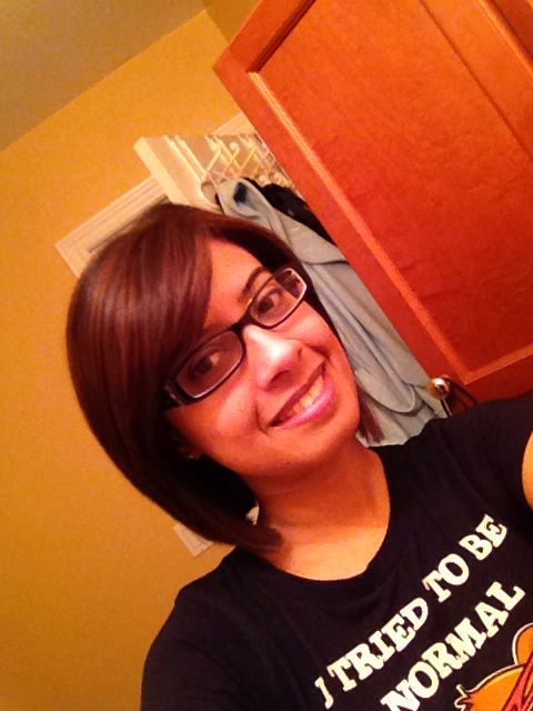 Short hair. Angled bob with side swept bangs. Dark hair with subtle high lights.