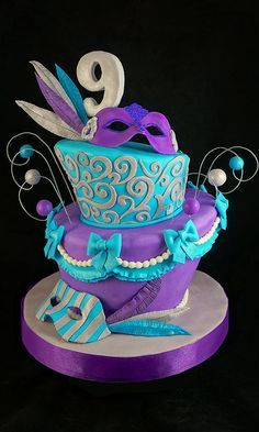 """Venetian Mask Topsy TurvyTapered, topsy turvy """"masks, feathers, bows, 9 topper, and balls on wires were all made from homemade gum paste, and 50/50 gum. and MMF. Fondant swirls on top tier were created with a custom silicone mold that I made."""" RobynYummCakes"""