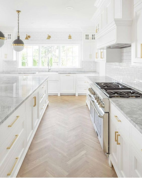 Magnificent white kitchen with classic design, herringbone floors, modern round pendant lights, and brass hardware. #whitekitchen #herringbone #classicdecor #modernfarmhouse #kitchendesign