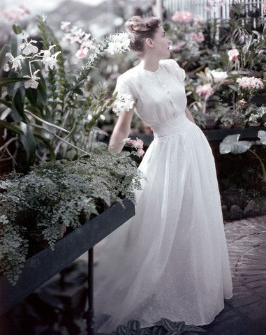 ca. 1947 --- Original caption: Model in white organdy dress by Marion McCoy, standing amongst pink flowers. --- Image by © Condé Nast Archive/Corbis