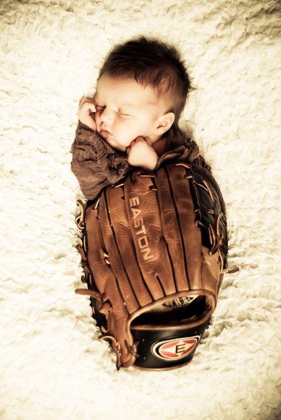 Newborn pictures in daddy's baseball glove.