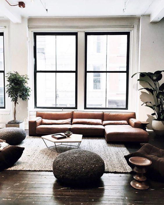 halbrundes Sofa in hellgrau und grüne Kissen