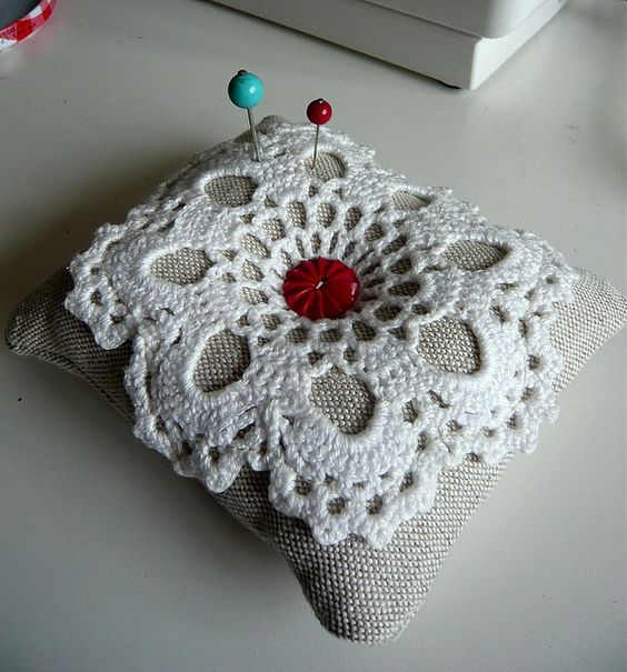 Pincushion with crocheted embellishment.