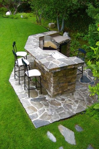 """BBQ is reinforced cinder block construction clad with stacked stone and flagstone. Random pieces of Kiawa Flagstone are used on upper BBQ countertop, BBQ deck and path leading to BBQ. BBQ sidewalls are clad with custom-cut dry stack Oakridge-Mountain Ledge stone. Lower countertop is done in 4"""" x 4"""" Bluestone tile. Natural stone boulders are added as accents throughout property."""