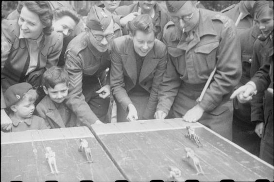 War Fair: Holidays at Home at a fete in Russell Square, London, 1943. Members of the Home Guard challenge a smiling young woman and two children to a 'horse race' at the Russell Square fete. The children were given a half the distance of the course as a head start. Members of the public crowd around them to watch the action.