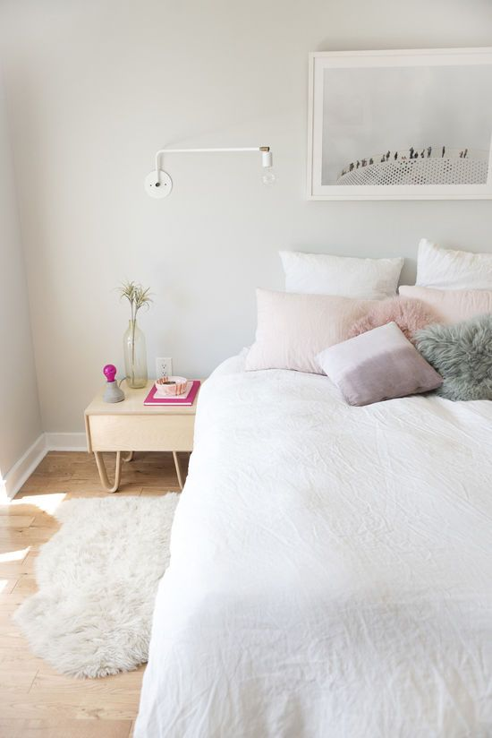 Simple serene bedroom with gray walls, white bedding, pastel throw pillows, and photograph above bed.