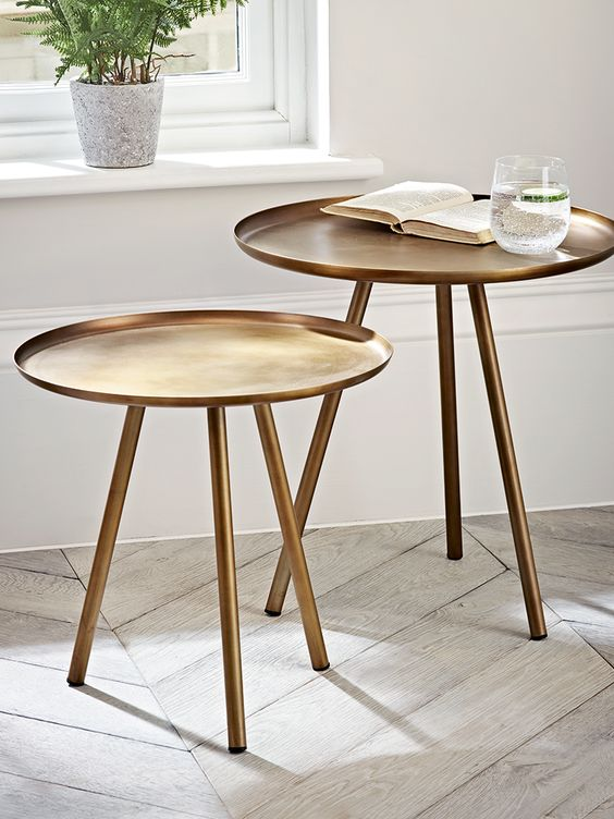 With three round tapered legs and a smooth lipped top, our pair of different sized tables are made from weighty iron with a striking burnished gold finish. These contemporary round side tables will add a touch of luxe to your living space, whether sat together besides the sofa or next to your favourite arm chair.