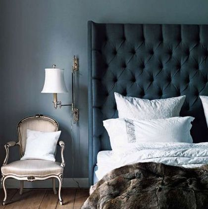 Tall tufted headboard in a moody blue with a bergère chair and wall lamp.