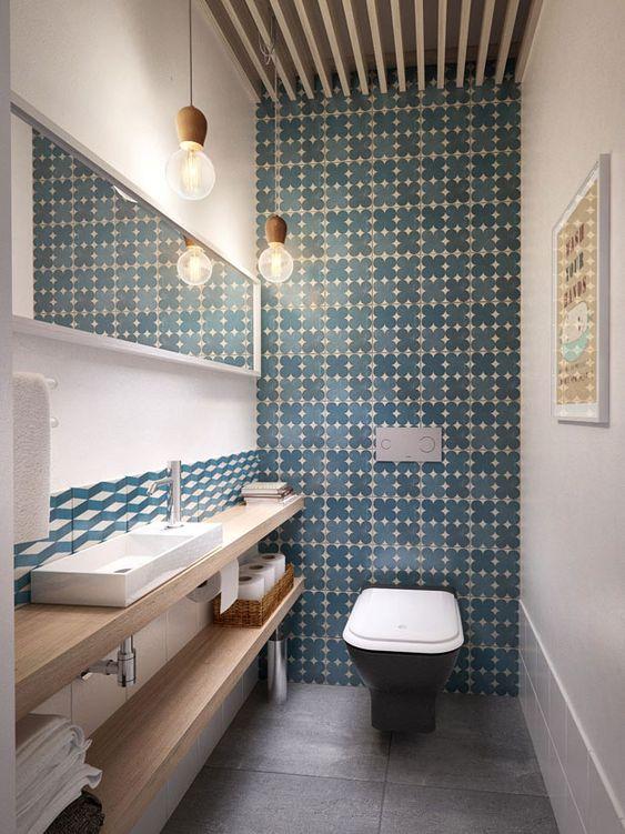 Toilettes avec carrelage gris foncé au sol, murs blancs avec carrelage bleu roi à motifs, miroir et étagères en bois