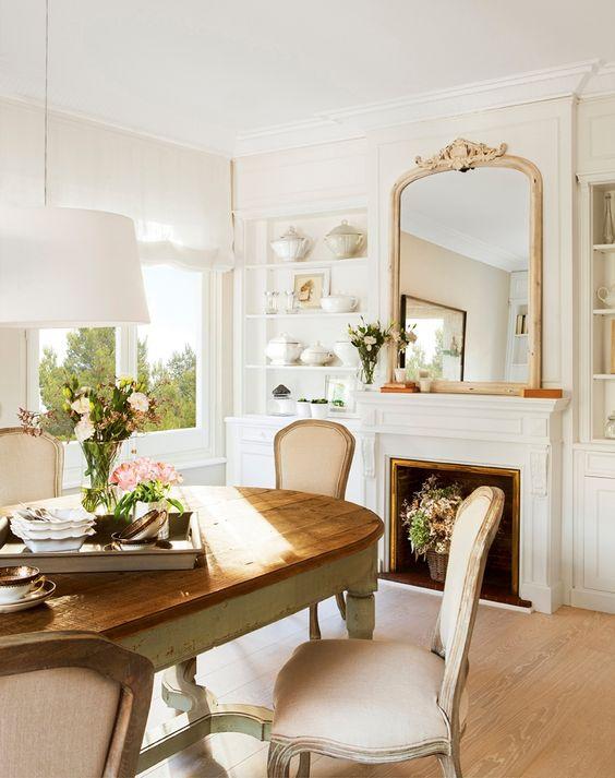 Comedor con chimenea, espejo, sillas clásicas y estanterías blancas con piezs de vajilla 399715
