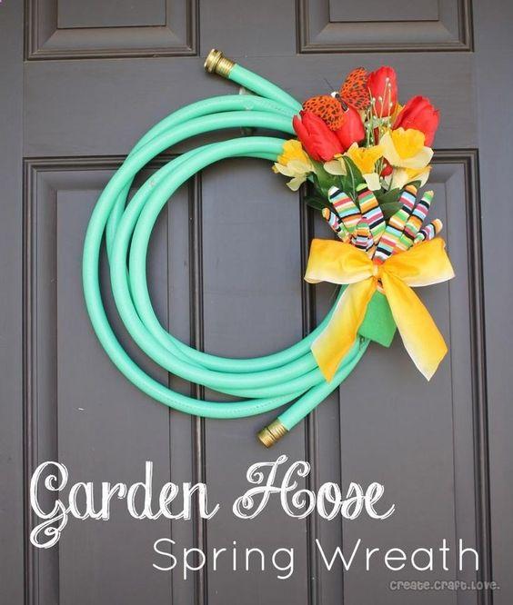 Garden Hose Spring Wreath DIY (updated link). materials: -15 foot garden hose -Twist tie -Silk flowers -Butterfly clip (optional, decor) -Garden gloves -Ribbon