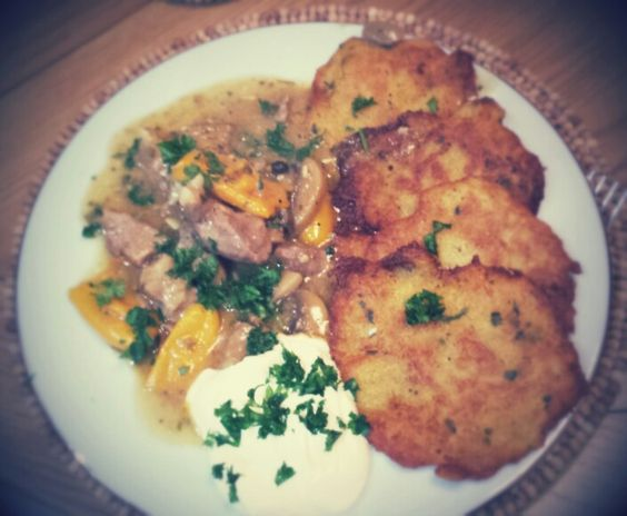 Potato pancakes with pork, mushroom and sweet peper stew served with sour cream